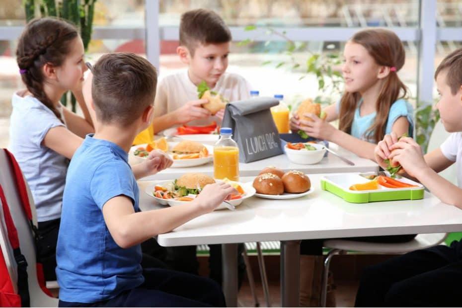 Kinder sitzen zusammen bei einem warmen Mittagessen
