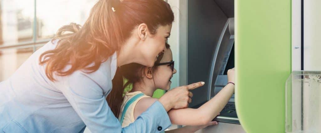 Mutter und Tochter heben Geld am Automaten ab